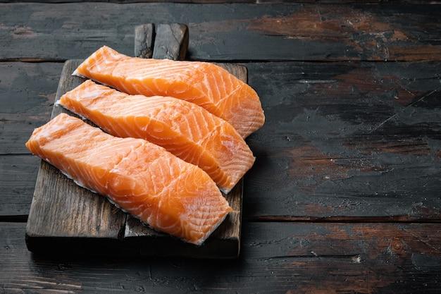 Set di porzioni di filetto di salmone, sul vecchio tavolo in legno con spazio per il testo