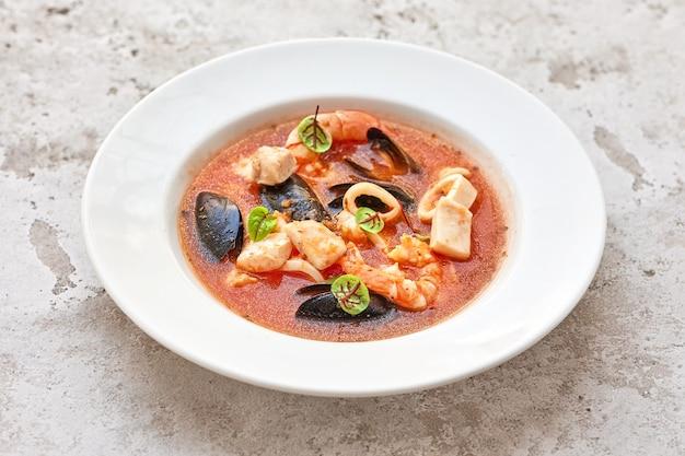 Porzione di zuppa di pomodoro con frutti di mare in piatto bianco sul tavolo del ristorante