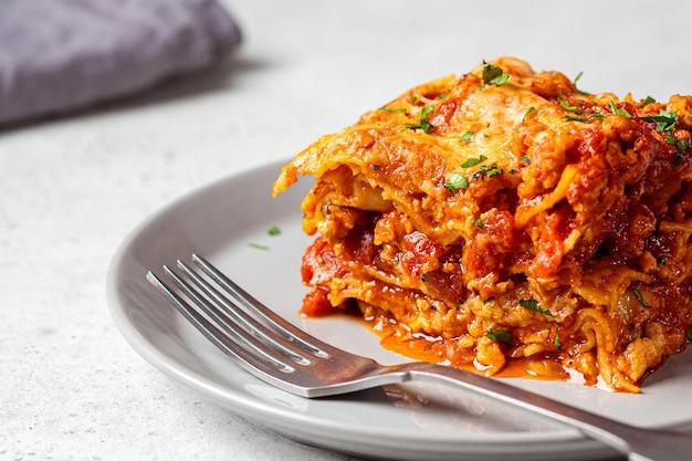 Porzione di lasagne italiane tradizionali con carne e formaggio su un piatto grigio. concetto di cucina italiana.