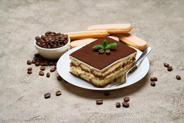 Porzione di dessert tiramisù italiano tradizionale e chicchi di caffè sul tavolo di cemento grigio
