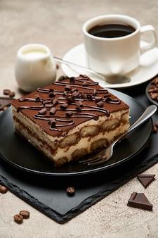 Porzione di dessert tiramisù italiano tradizionale e tazza di caffè espresso sul tavolo di cemento grigio
