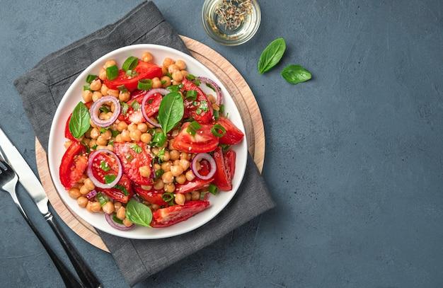 Una porzione di insalata di verdure con ceci, pomodori, erbe fresche e olio d'oliva. cibo vegetariano e sano.