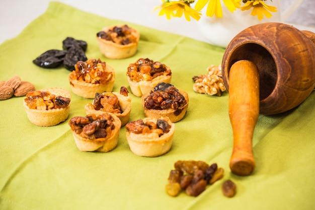Tartellette porzionate con ripieno di noci candite e frutta secca mortaio in legno di fondo