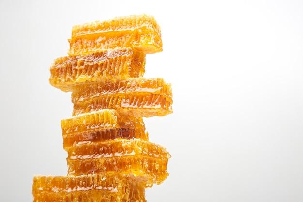 Porzioni di favo fresco su uno sfondo bianco. cibo naturale vitaminico. prodotto del lavoro delle api