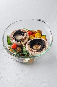 Portobello e ingredienti per la cottura del formaggio cheddar, pomodorini e salvia in vaso di vetro su sfondo bianco vista laterale.