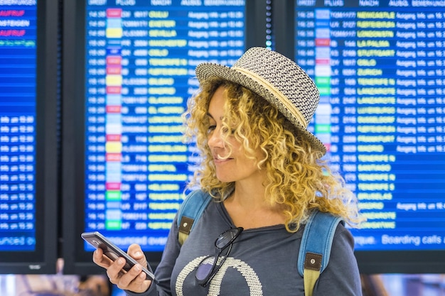 Portrai di bella donna caucasica adulta viaggia e controlla l'app sullo smart phone per partire e iniziare dai display dell'aeroporto con il tempo nella tecnologia di superficie e nella connessione internet persone moderne