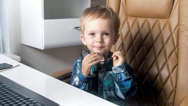 Portrai del ragazzino sorridente sveglio che si siede sulla sedia dell'ufficio dietro la scrivania in ufficio.