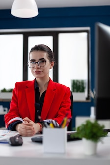 Ritratto di donna d'affari fiduciosa seduta alla scrivania nell'edificio sul posto di lavoro dell'ufficio aziendale, con le dita incrociate con gli occhiali che guarda l'obbiettivo. grafici e grafici finanziari.