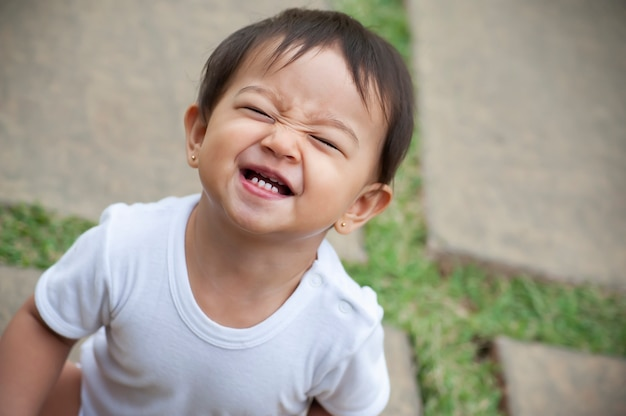 Ritratto di una ragazza dall'aspetto asiatico di 1 anno. scena divertente, fare una smorfia. scena all'aperto. copia spazio