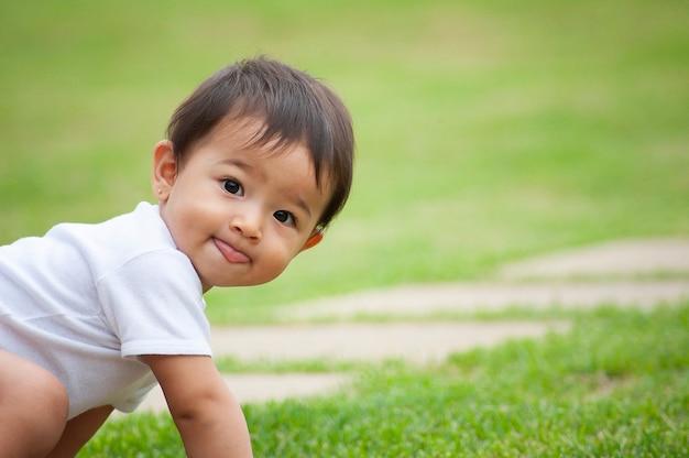 Ritratto di una ragazza dall'aspetto asiatico di 1 anno. scena divertente, che mostra la lingua. scena all'aperto. copia spazio