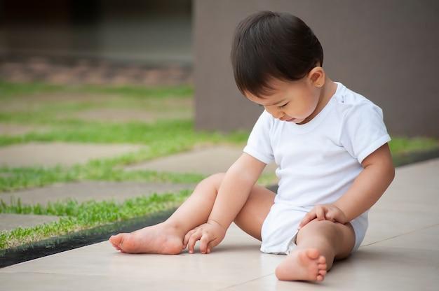 Ritratto di una ragazza dall'aspetto asiatico di 1 anno che gioca da solo nel cortile. scena all'aperto. copia spazio