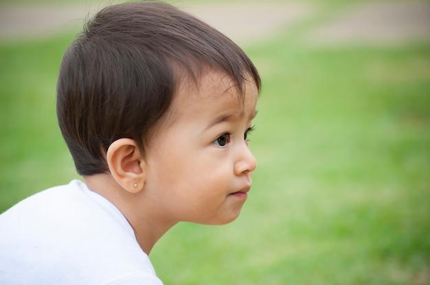 Ritratto di una ragazza dall'aspetto asiatico di 1 anno che gioca da solo nel cortile. scena all'aperto. messa a fuoco selettiva. copia spazio