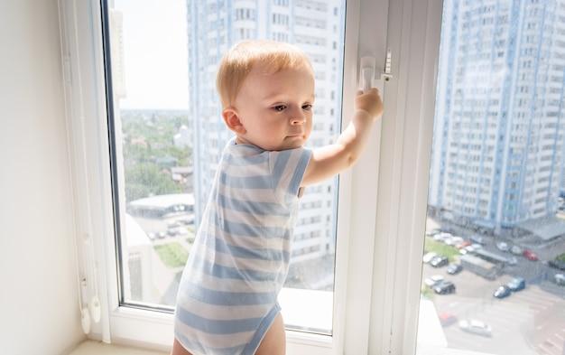 Ritratto di un bambino di 10 mesi che cerca di aprire la finestra