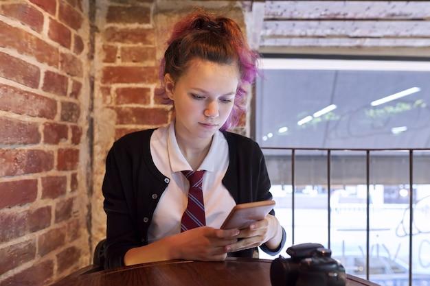 Ritratto di una ragazza adolescente di 15 anni in uniforme scolastica con cravatta seduta su una sedia guardando smartphone, sfondo muro di mattoni, finestra spazio copia