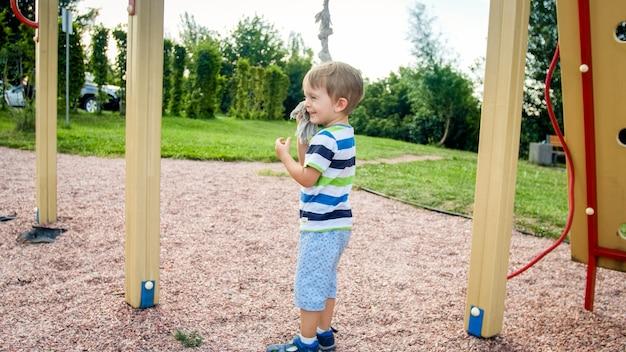 Ritratto di 3 anni che gioca nel parco giochi e cerca di arrampicarsi sulla grande corda del parco