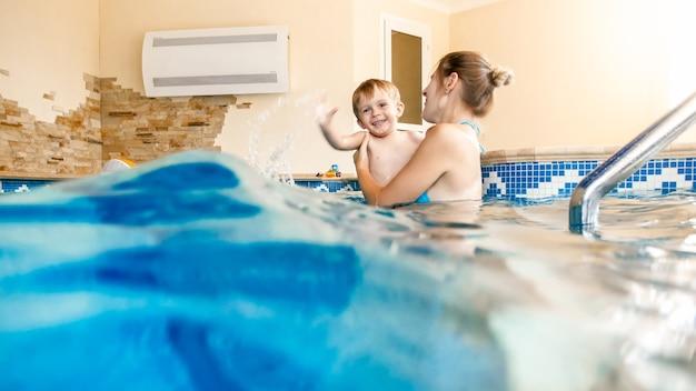 Ritratto di un bambino di 3 anni con una giovane madre che nuota nella piscina interna. bambino che impara a nuotare e a fare sport. famiglia che si diverte e si diverte in acqua