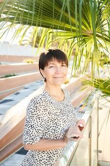 Ritratto di donna d'affari caucasica felice di 50 anni in posa e sorridente nel parco, signora reale sana adulta