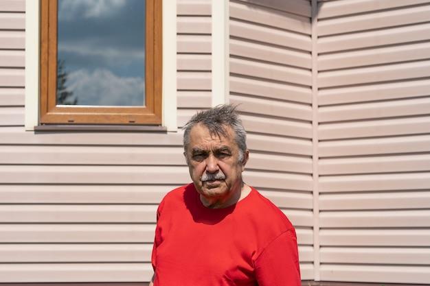 Ritratto di un uomo anziano di 70 anni prima della casa di campagna in giardino, in giardino, in estate.
