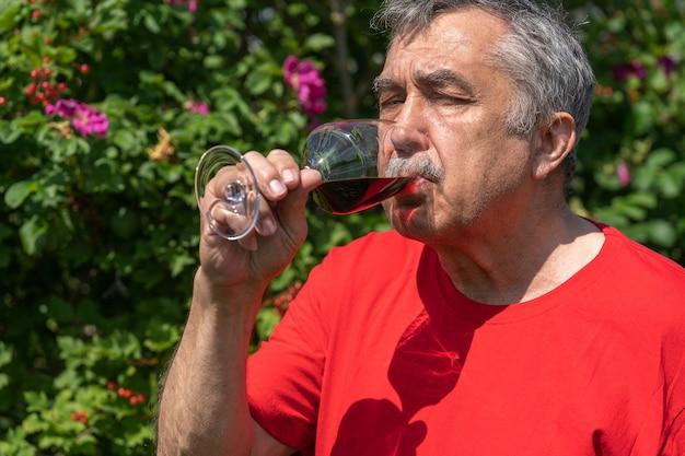 Il ritratto dell'uomo anziano di 70 anni beve il vino rosso nel giardino, estate.