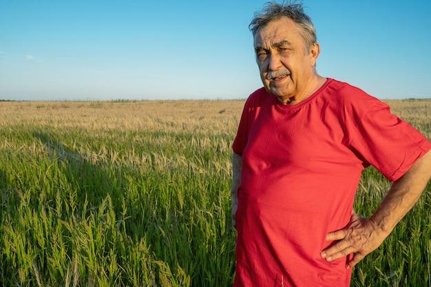 Ritratto di un uomo anziano di 70 anni con una maglietta rossa che guarda con calma e attenzione la telecamera, nel campo, prima del tramonto.