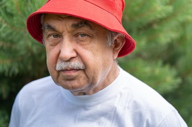 Ritratto di un uomo anziano di 70 anni con una maglietta bianca e un cappello rosso che guarda con calma e attenzione la telecamera, nel giardino di campagna.