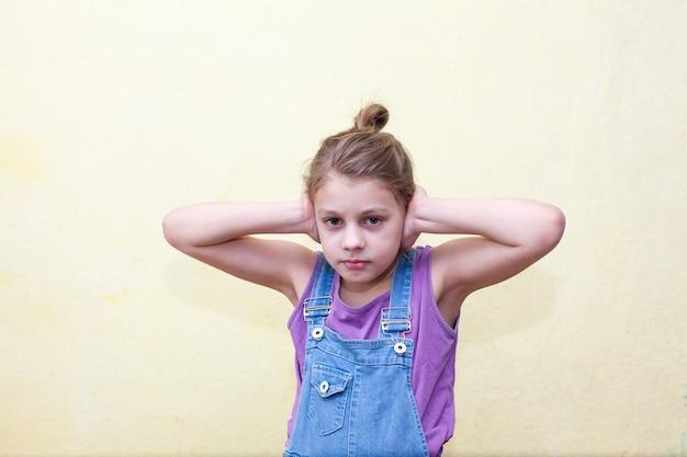 Ritratto di una bambina di 8 anni sulla parete gialla, spaventata che copre le orecchie con le mani