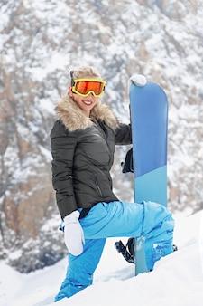 Ritratto di snowboarder femminile attivo in piedi in cima allo sfondo della montagna copia spazio