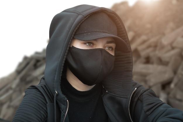 Ritratto di un attivista vestito con abiti neri, maschera e guanti su uno sfondo di pietre