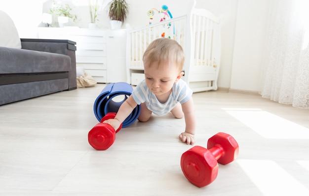 Ritratto di adorabile bambino che si esercita con i manubri sul pavimento in soggiorno