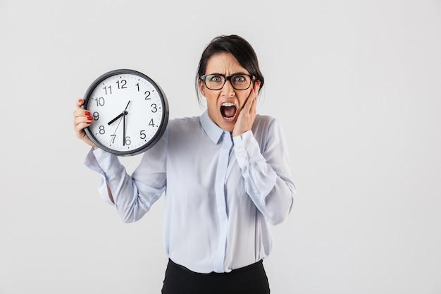 Ritratto di adorabile imprenditrice indossando occhiali da vista tenendo l'orologio rotondo in ufficio, isolato sopra il muro bianco