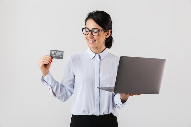 Ritratto di adorabile imprenditrice indossando occhiali da vista in possesso di laptop d'argento e carta di credito in ufficio, isolato sopra il muro bianco