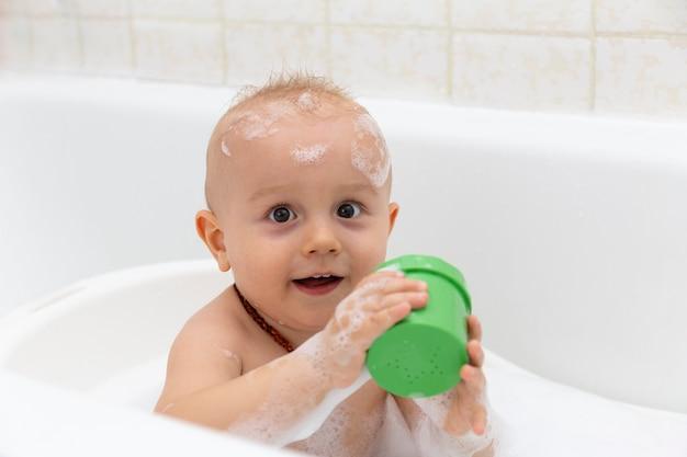 Un ritratto del ragazzino curioso adorabile che lava nella vasca da bagno