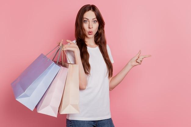 Ritratto di adorabile ragazza eccitata tenere le borse del negozio diretto lo spazio vuoto del dito che promuove la vendita su sfondo rosa