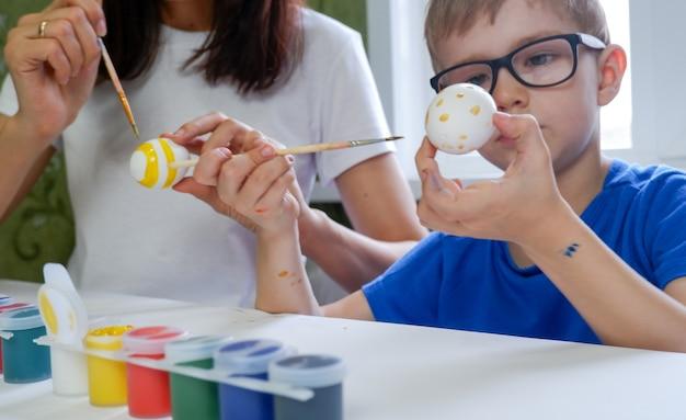 Ritratto di adorabile ragazzino che dipinge le uova di pasqua con sua madre.