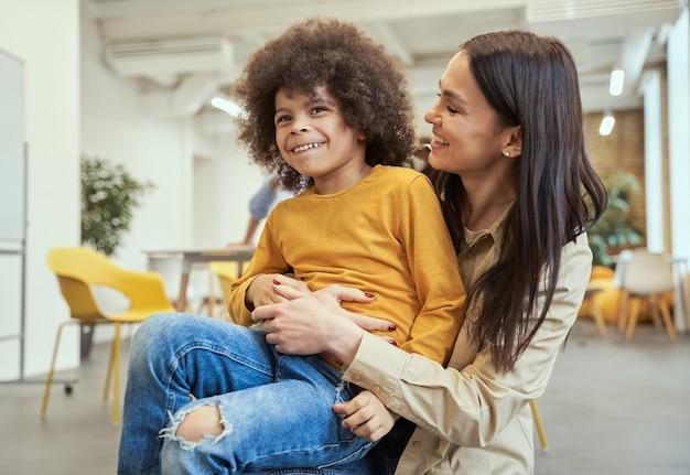 Ritratto di un ragazzino adorabile con i capelli afro che sorride divertendosi insieme a bei giovani
