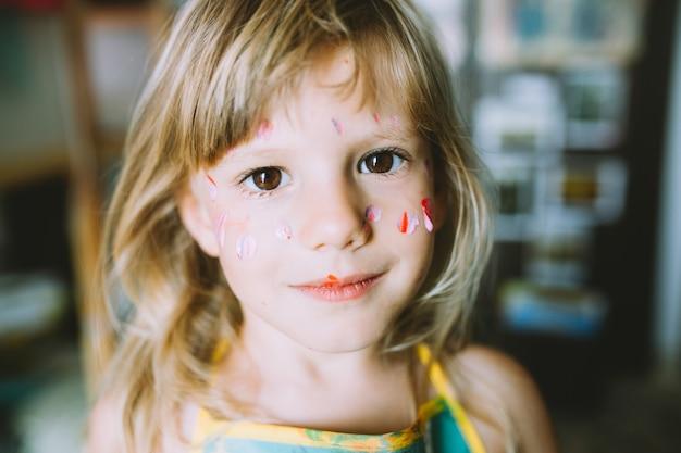 Ritratto di adorabile bambina con vernice sul viso