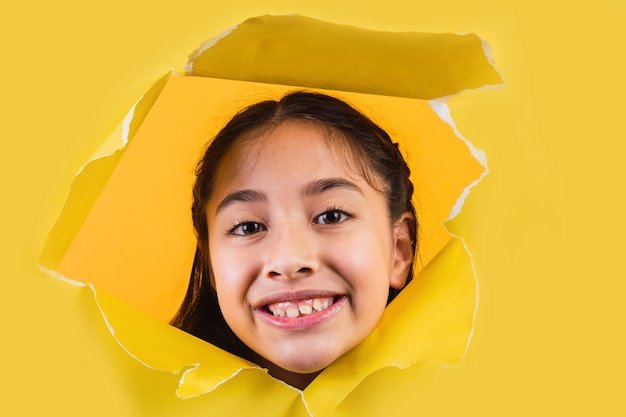Ritratto di un'adorabile bambina sorridente su sfondo giallo.