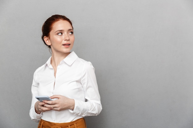 Ritratto di una donna d'affari rossa adorabile 20s in abbigliamento formale che tiene in mano lo smartphone e guarda il copyspace in ufficio isolato su grigio