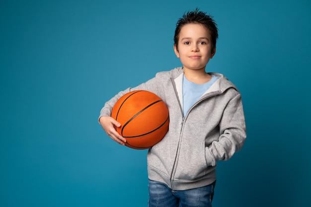 Ritratto di un adorabile bambino sportivo che tiene una palla per giocare a basket in mano, guardando la fotocamera e in piedi