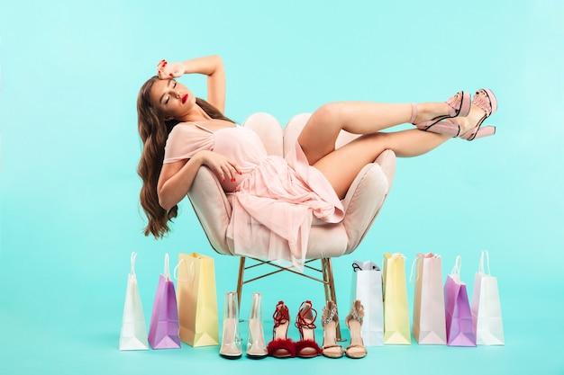 Ritratto di adorabile donna stanca 20s seduto sulla poltrona rosa dopo lo shopping con un sacco di sacchetti di acquisto, isolato sopra la parete blu