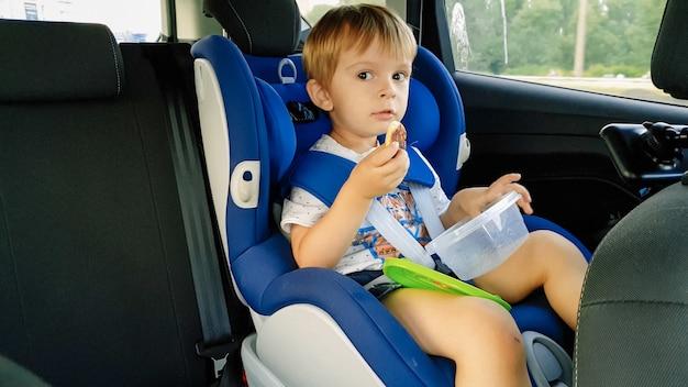 Ritratto di un bambino adorabile seduto nel seggiolino di sicurezza dell'auto per bambini e che mangia biscotti