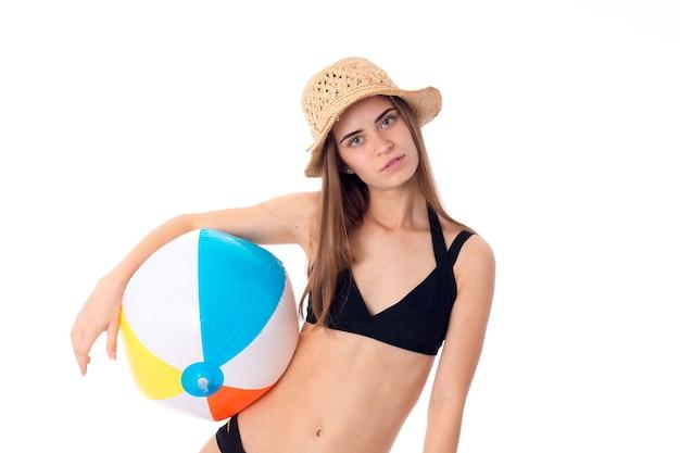 Ritratto di donna adorabile in costume da bagno nero con pallone da spiaggia isolato sul muro bianco