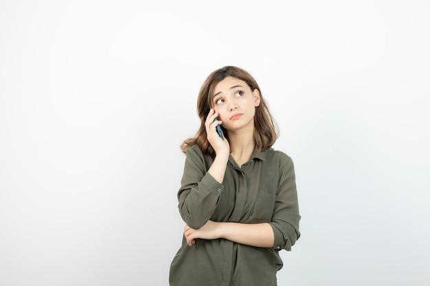 Ritratto di donna adorabile che comunica tramite cellulare sopra bianco.