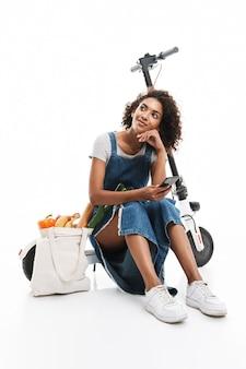 Ritratto di donna adorabile che utilizza il cellulare mentre è seduto su uno scooter elettronico con una borsa della spesa isolata su un muro bianco