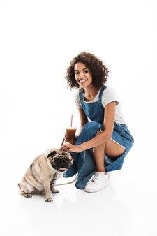 Ritratto di una donna adorabile che indossa una tuta di jeans che tiene in mano una tazza di plastica mentre posa con il suo carlino isolato su un muro bianco