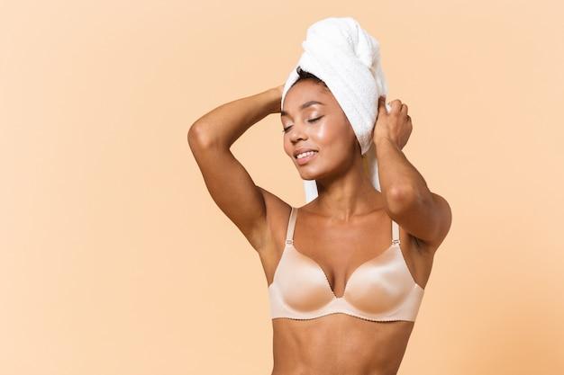 Ritratto di donna adorabile avvolta in un asciugamano e indossa lingerie bianca, in piedi isolato sul muro beige