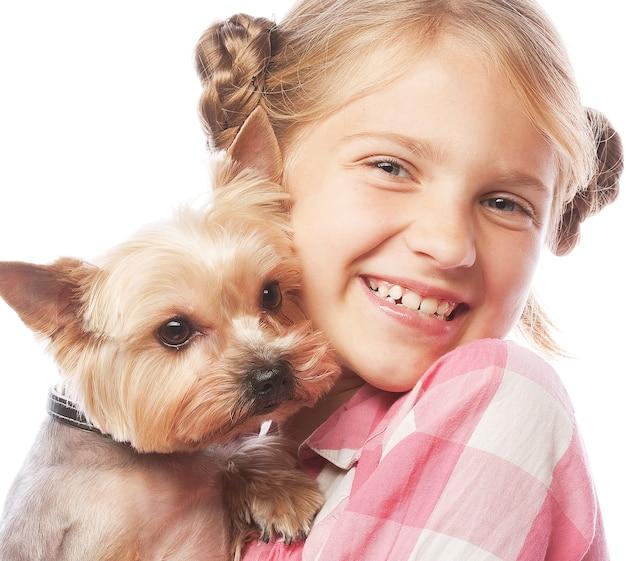 Ritratto di un'adorabile ragazza sorridente che tiene in braccio un cucciolo di yorkshire terrier