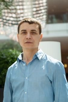 Ritratto di un uomo adulto di razza caucasica con una camicia blu.
