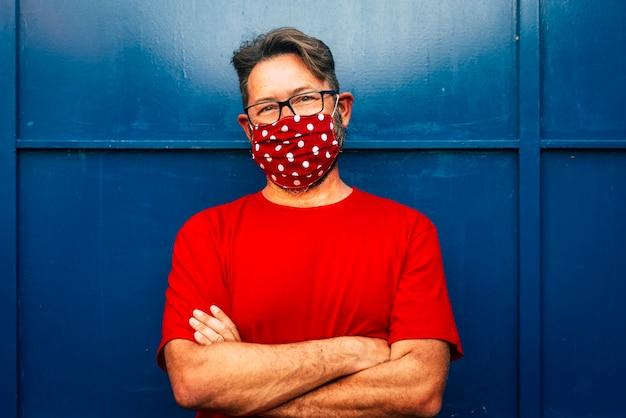 Ritratto di uomo adulto con gli occhiali che indossano maschera rossa e camicia con porta blu sullo sfondo - concetto di persone e maschera di protezione per l'epidemia di coronavirus covid-19 emergenza pandemica