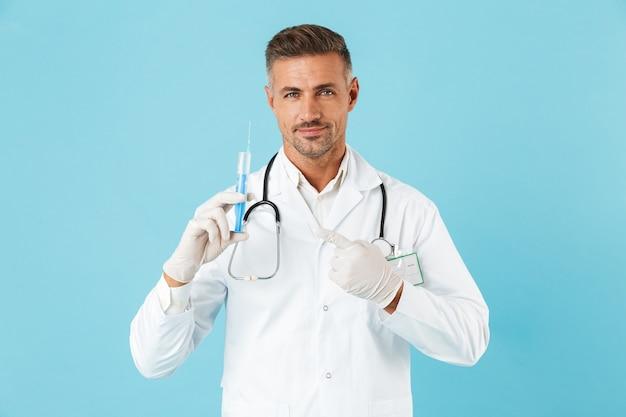 Ritratto del medico adulto con lo stetoscopio in guanti che tengono la siringa, in piedi isolato sopra la parete blu